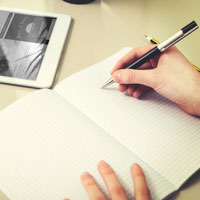 hand writing in journal with a tablet and earbuds nearby