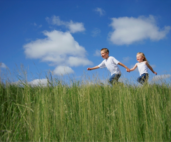 children running through a field in spring