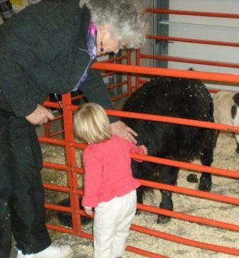 woman and child petting a farm animal