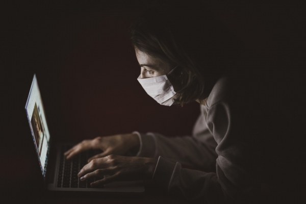 adult women in front of a laptop and wearing a face mask