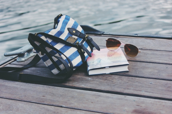 bag, book and sunglasses on pier by lake