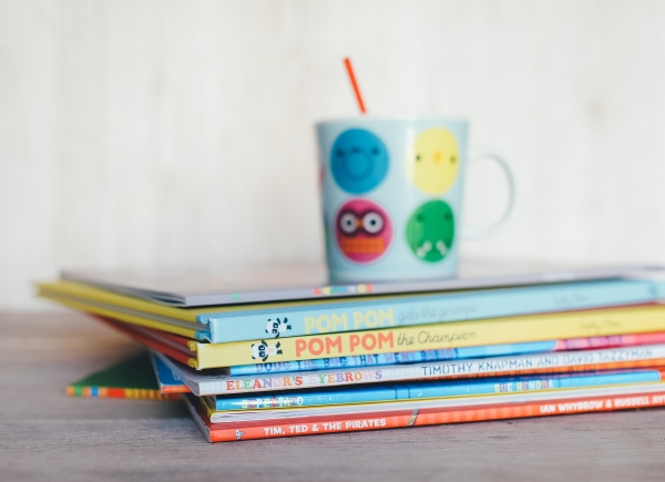 stack of children's books and a whimsical cup