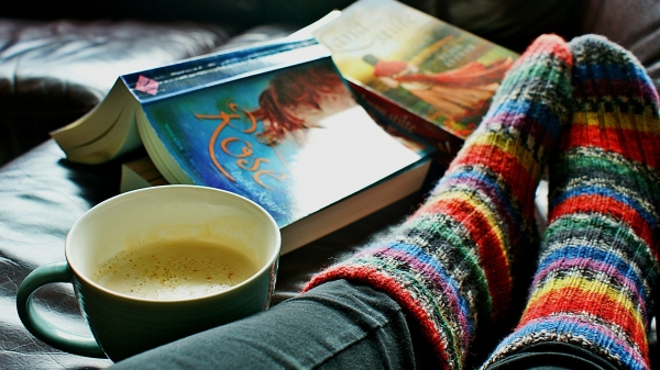 feet in cozy socks with a book and coffee