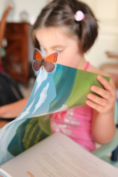 girl reading book with a butterfly on the page