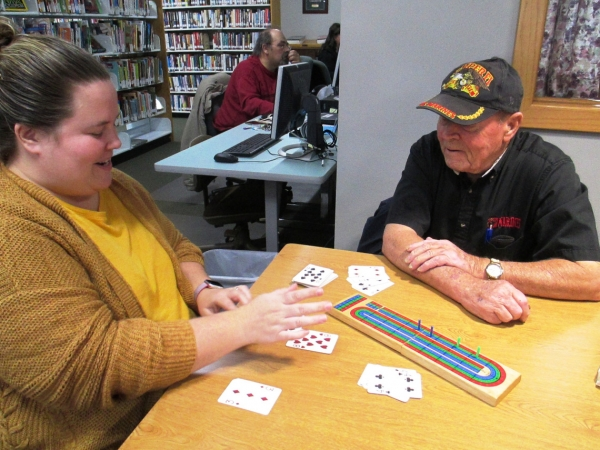 Patrons play cribbage at the Spencer Branch library in November 2018, while others use the public computers.