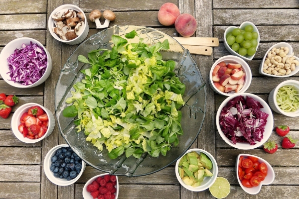 bowl of chopped lettuce with berries, nuts and vegetables around the bowl