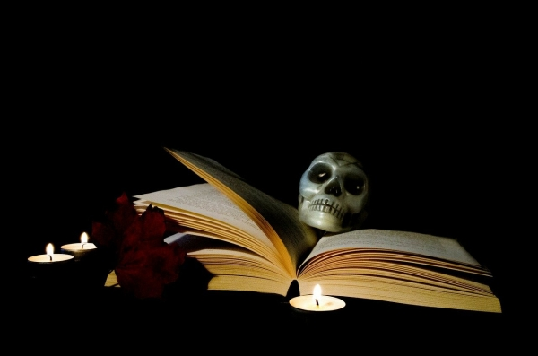 a book with a skull on top of it surrounded by candles