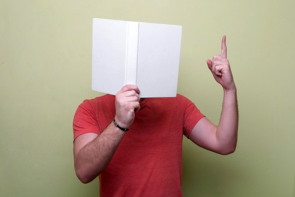 man with a book in front of his face