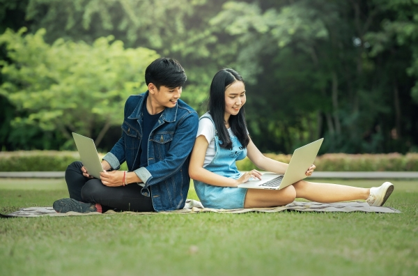 teen boy and girl with laptop computers