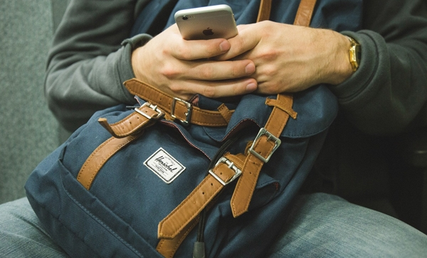 student with backpack and smartphone