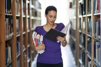 woman carrying books in library